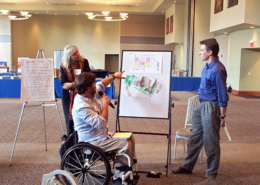 Man in a wheelchair points to a whiteboard with two onlookers.