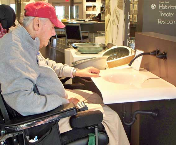Man using wheelchair next to an accessibly-designed sink.