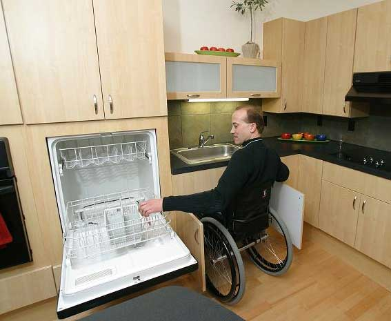 Man in wheelchair using accessible dishwasher