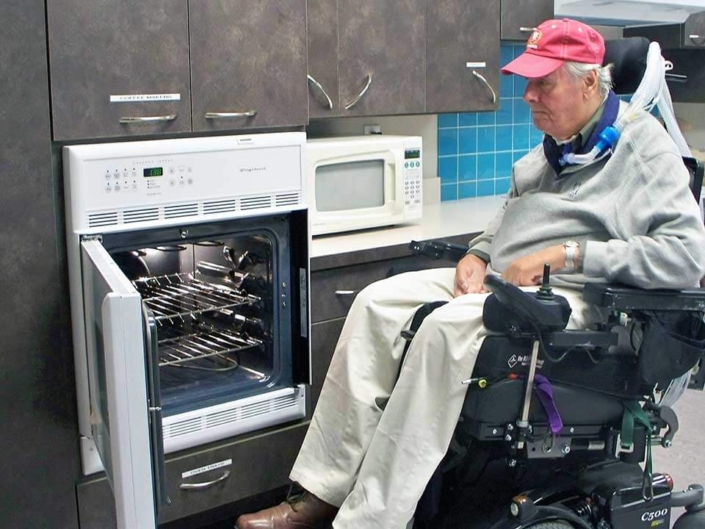 Man using wheelchair next to an accessibly-designed oven.