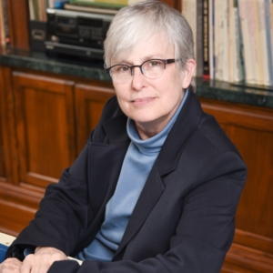 Gina has fair skin and white hair. She is seated at a table and leaning toward the camera. She is wearing floating frame glasses, a powder blue turtleneck and a black blazer.